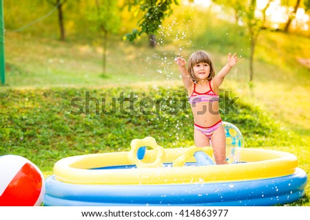 Little girl with ball in the garden swimming pool. - stock photo