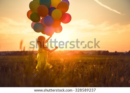 Little girl with balloons in the field - stock photo