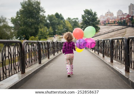 Little girl with balloons in the park - stock photo