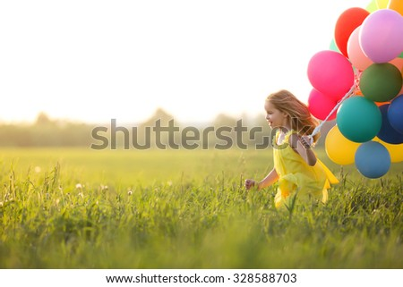 Little girl with balloons outdoors - stock photo