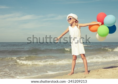 Little girl with balloons  standing on the beach at the day time - stock photo
