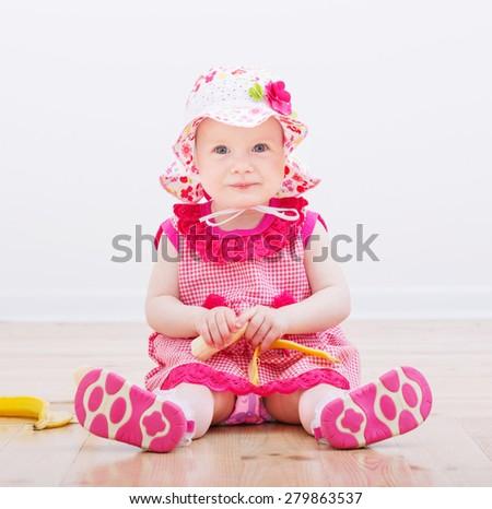 little girl with banana indoor - stock photo