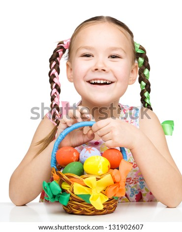 Little girl with basket full of colorful eggs preparing for Easter, isolated over white - stock photo