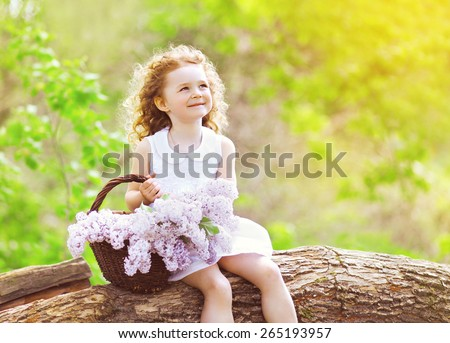 Little girl with basket of lilac flowers sitting and enjoying sunny summer day - stock photo