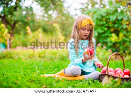 Little girl with basket of red apples in sunny autumn day - stock photo