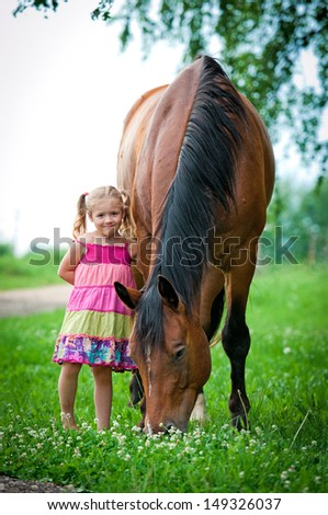 Little girl with big horse - stock photo