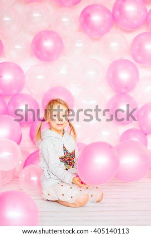 little girl with blond hair playing with pink and beige balloons. Happy Birthday - stock photo