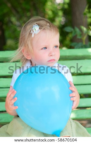 Little girl with blue air balloon sitting on bench - stock photo