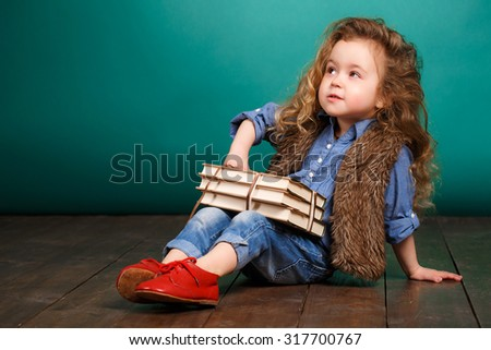 Little girl with books. Child studying. Schoolchild. Schoolgirl. studio portrait. school preparation. baby holding bunch of books. education. pupil.  - stock photo