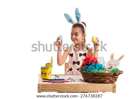 Little girl with bunny ears sitting at table and choose Easter egg - stock photo