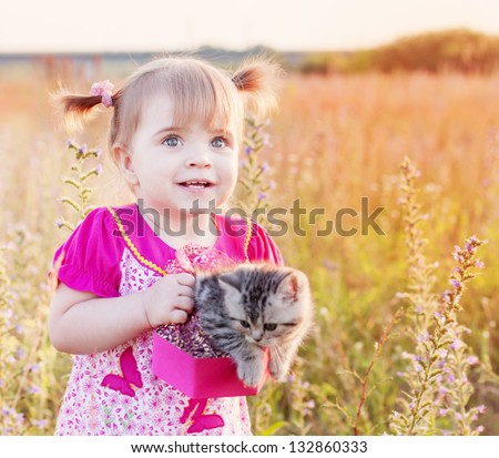 little girl with cat outdoor - stock photo