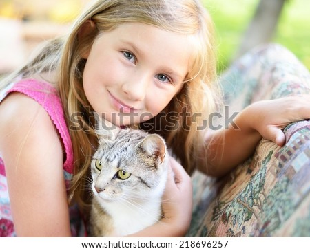 Little girl with cat. Outdoors. - stock photo