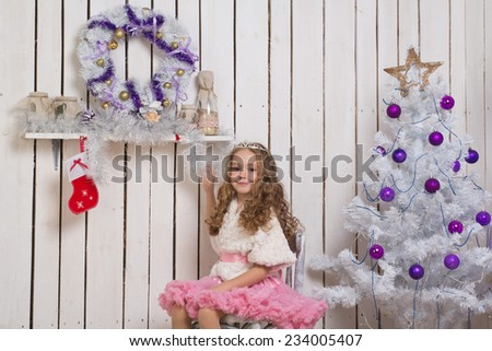 Little girl with christmas fir tree decorations, focus on girl - stock photo