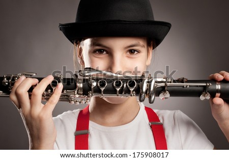 little girl with clarinet on a gray background - stock photo