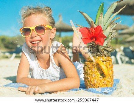 Little girl with cocktail on the beach vacation. - stock photo