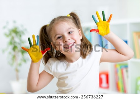 little girl with color hands in paint playing in nursery - stock photo