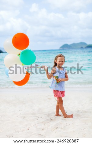 Little girl with colorful balloons at beach celebrating birthday during summer vacation - stock photo