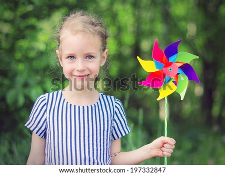 Little girl with colorful pinwheel in the park. - stock photo