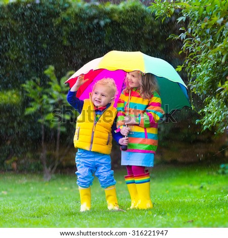 Little girl with colorful umbrella playing in the rain. Kids play outdoors by rainy weather in fall. Autumn fun for children. Toddler kid in raincoat and boots walking in the garden. Summer shower. - stock photo