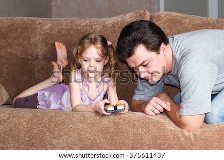 little girl with dad playing on the couch - stock photo