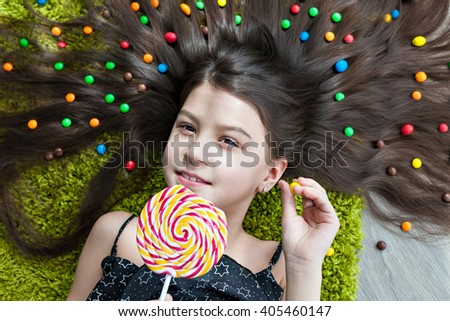 Little girl with dark hair lying on the floor among the sweets. Top view of a big yellow and pink lollipops in hands. Many candies in her hair. the smile, the joy on a child's face. - stock photo