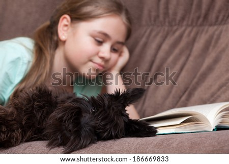 Little girl with dog reading book while lying on the sofa at home. Focus on foreground - stock photo