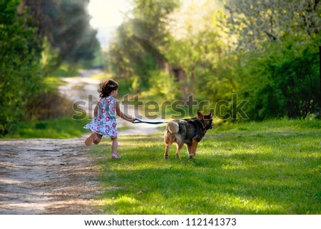 Little girl with dog running on the road to the sun - stock photo