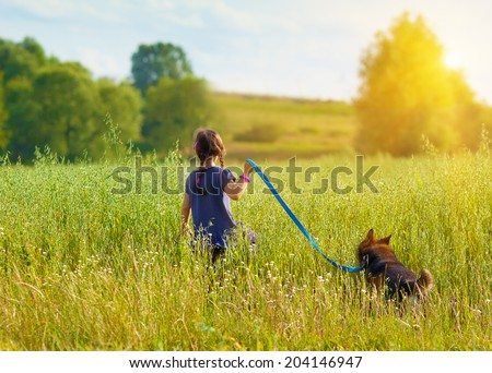 Little girl with dog walking on the field back to camera - stock photo