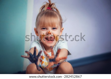 Little Girl with drawings on the face shows his hands in paint - stock photo