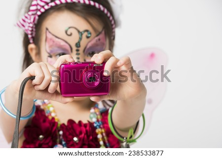 Little girl with face painting holding  a snapshot camera - stock photo