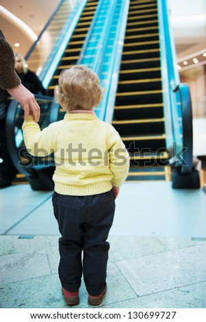 Little girl with father standing in front of escalator - stock photo