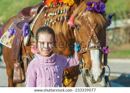 Little girl with festive horse in summer city Park. - stock photo