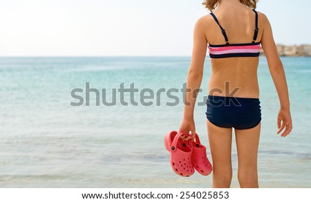 Little girl with flip flops standing on the beach. - stock photo