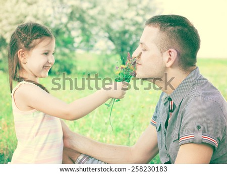 Little girl with flowers in hand and uncle smiling and enjoy in beautiful day - stock photo