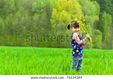 Little girl with flowers on green field - stock photo
