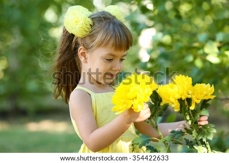 Little girl with flowers outside - stock photo