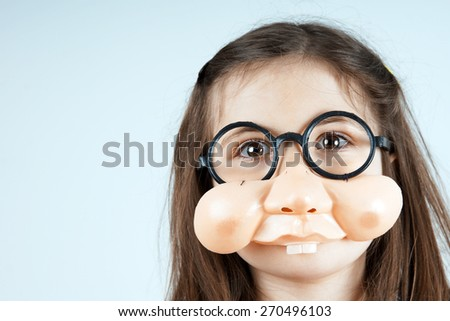 Little girl with funny fake nose and round glasses  - stock photo