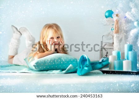 little girl with gifts at the Christmas tree - stock photo