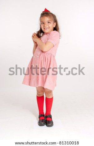 Little girl with glasses and a happy funny expression - stock photo