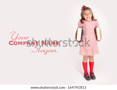 Little girl with glasses and a happy funny expression holding a pair of big books  - stock photo