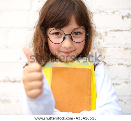 Little girl with glasses holding a books in their hands - stock photo