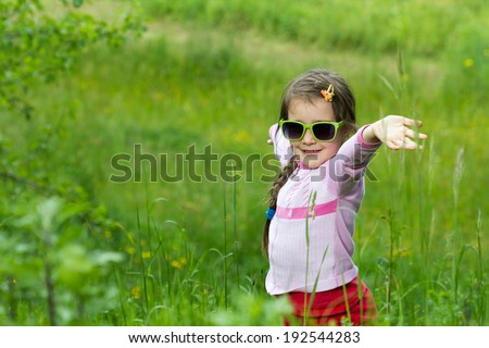 Little girl with glasses posing in grass - spring time - stock photo