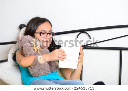 Little girl with glasses reading a book while holding her teddy bear - stock photo