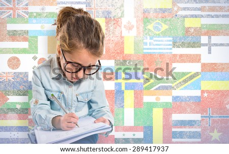 Little girl with glasses studing over flags background - stock photo