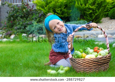 Little girl with great autumn harvest of tomatoes in baskets - stock photo