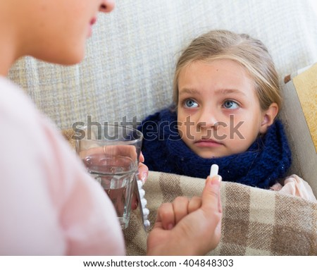 Little girl with grippe receiving pills from worried mother - stock photo