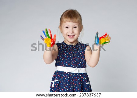 little girl with hands in paint on white - stock photo