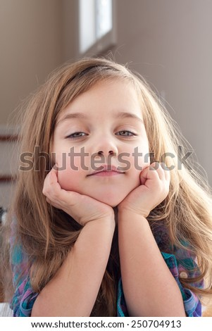 little girl with hands up her chin. - stock photo
