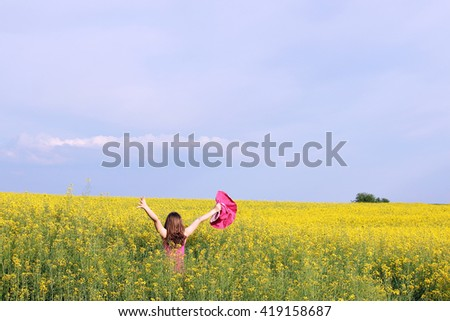 little girl with hands up in yellow  - stock photo
