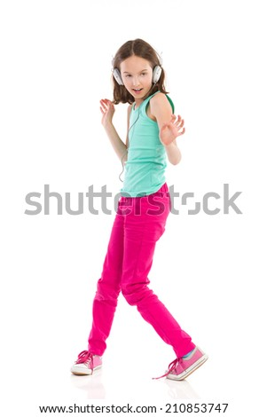 Little girl with headphones dancing and singing. Full length studio shot isolated on white. - stock photo